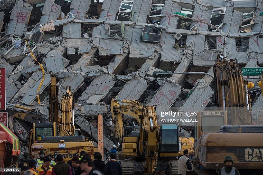A general view shows excavator vehicles and rescue workers in front of a building (background) which collapsed in the 6.4 magnitude earthquake, in the southern Taiwanese city of Tainan early on February 9, 2016. Rescuers are set to start using diggers and extractors to remove giant concrete slabs once they have ensured all residents from the upper parts of the rubble have been freed. AFP PHOTO / ANTHONY WALLACE / AFP / ANTHONY WALLACE