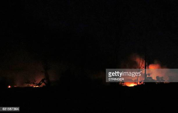 A general view shows flames and smoke at the Mezzah military airport on the southwestern outskirts of the capital Damascus following an explosion...