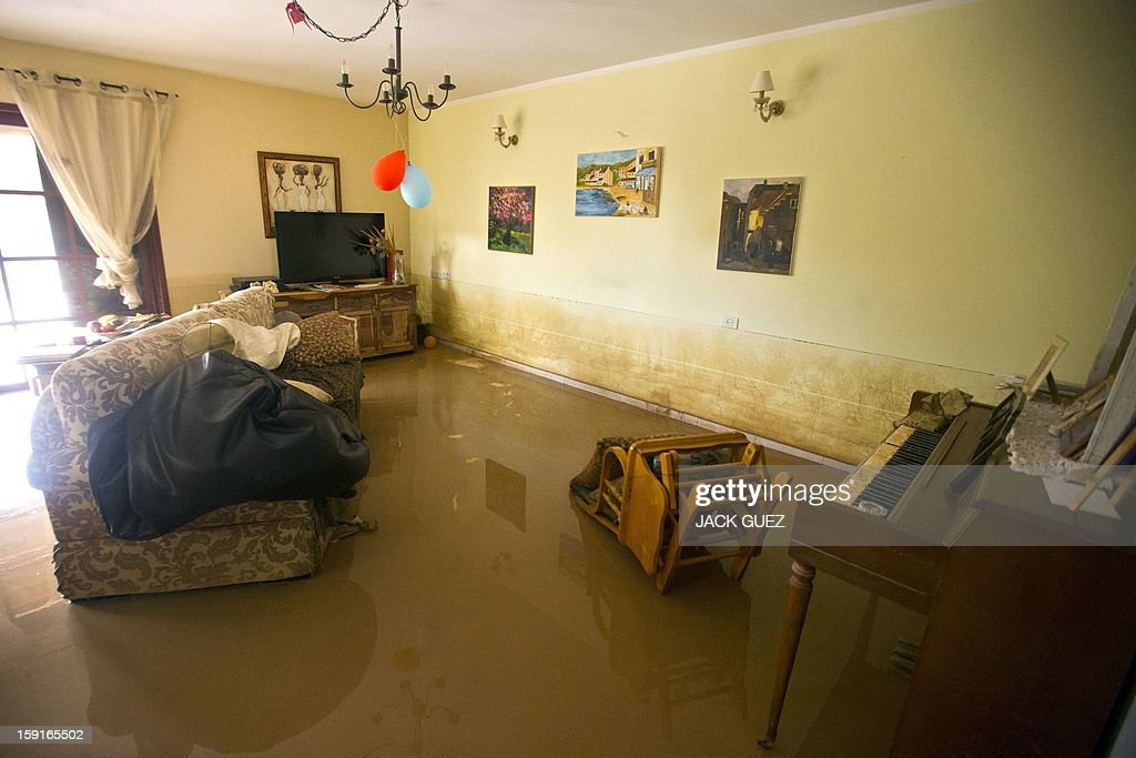 A general view shows flooding on the ground floor of a house caused by heavy rains overnight in Beit Hefer near the Mediterranean coastal city of Netanya, north of Tel Aviv, on January 9, 2013. Israel and the Palestinian territories have been lashed by heavy rain and high winds since January 6, which has caused flooding across the region. AFP PHOTO / JACK GUEZ