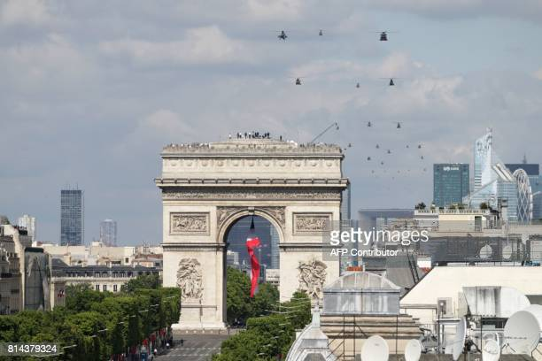 A general view shows French military helicopters flying over the Arc de Triomphe during the annual Bastille Day military parade on the ChampsElysees...