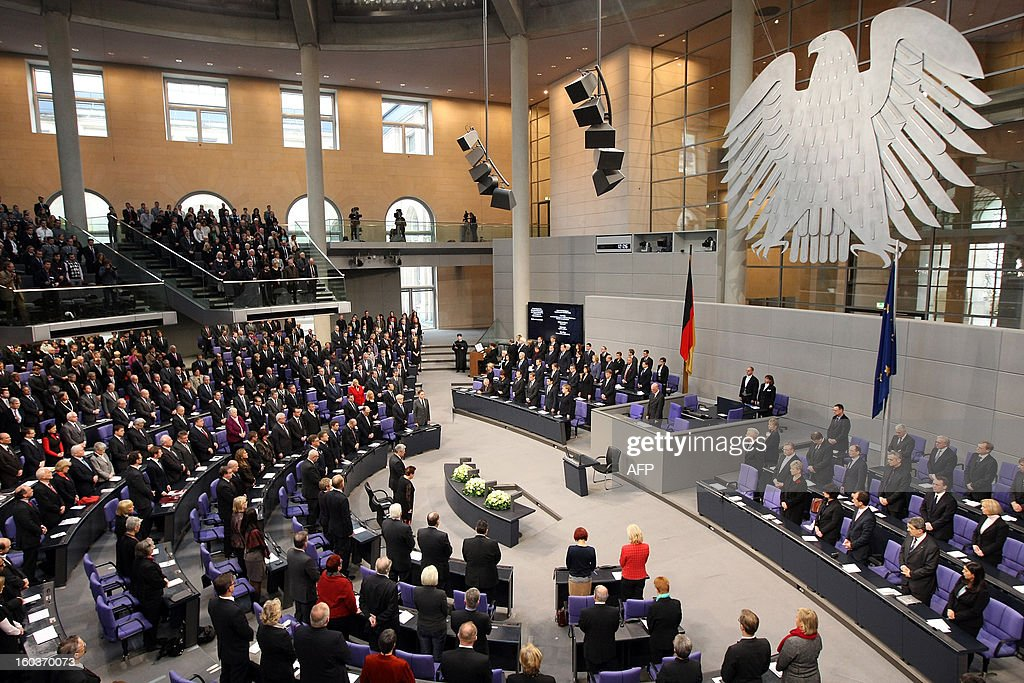 A general view shows German Chancellor Angela Merkel (C, R), members of German government and parliament standing as a cantor sings at the German lower house of Parliament Bundestag, in Berlin on January 30, 2013 during a memorial held by deputies for the victims of the Nazi regime, and the anniversary of the liberation of Auschwitz concentration camp on January 27, 1945. Since the date fell on a Sunday this year, the event was held later, on the day marking 80 years since Adolf Hitler became chancellor. BERRY