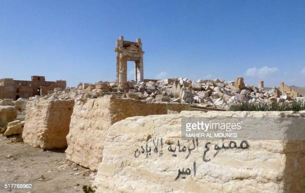 A general view shows graffiti on a stone reading in Arabic 'Shooting without the permission of the chief is prohibited' near the remains of the...
