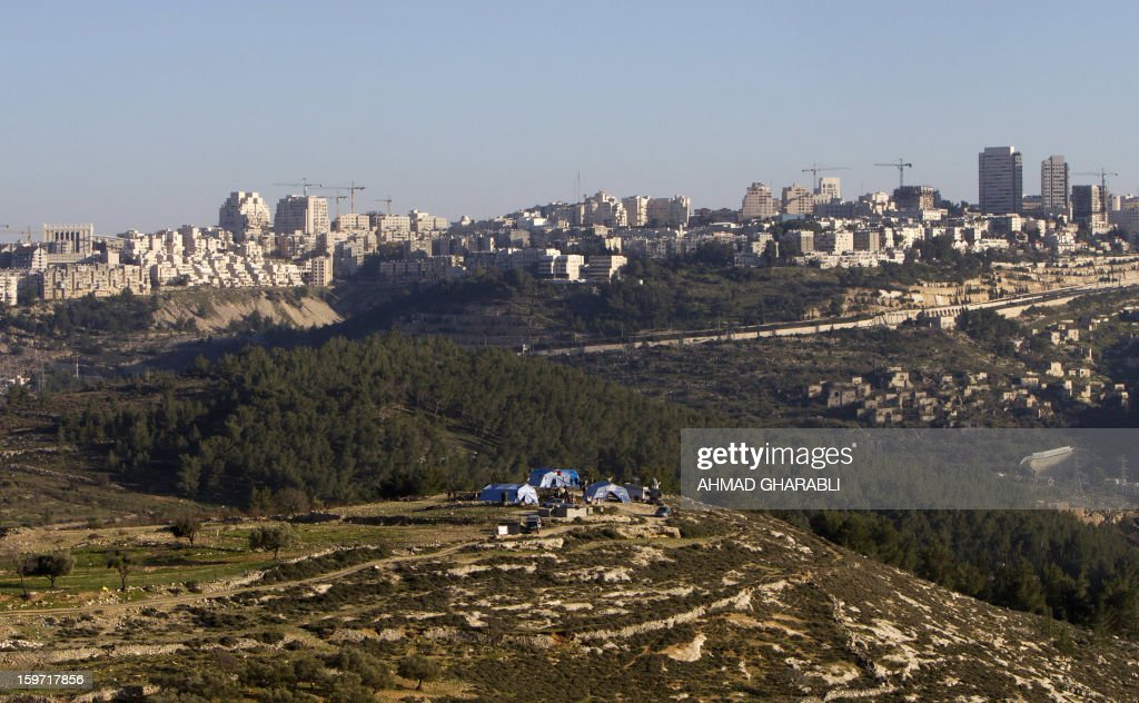 A general view shows Jerusalem in the background and Palestinian protestors gathering next to newly erected tents on January 19, 2013. Some 200 Palestinians gathered at a new encampment protesting for the second consecutive day Israel's intention to confiscate land. AFP PHOTO/AHMAD GHARABLI