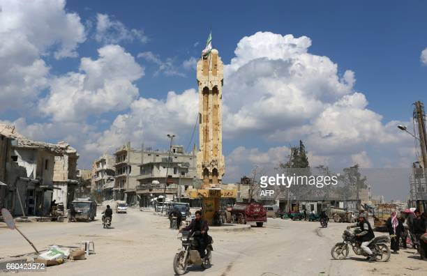 TOPSHOT A general view shows people passing along a destroyed street in alBab on March 29 2017 a month after Turkishbacked rebels recaptured the...