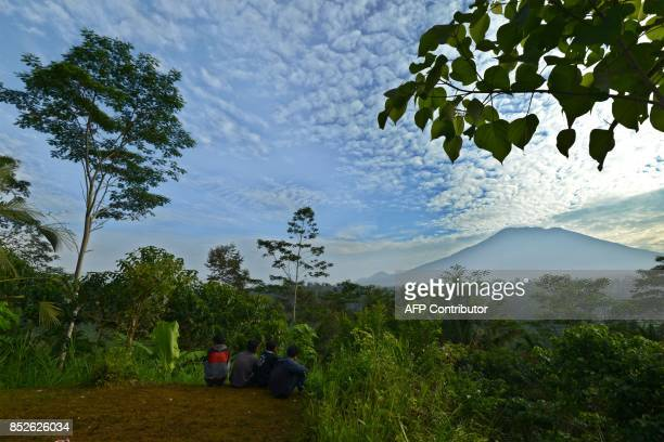 A general view shows people sitting before Mount Agung in Karangasem on the Indonesian resort island of Bali on September 24 2017 Authorities have...