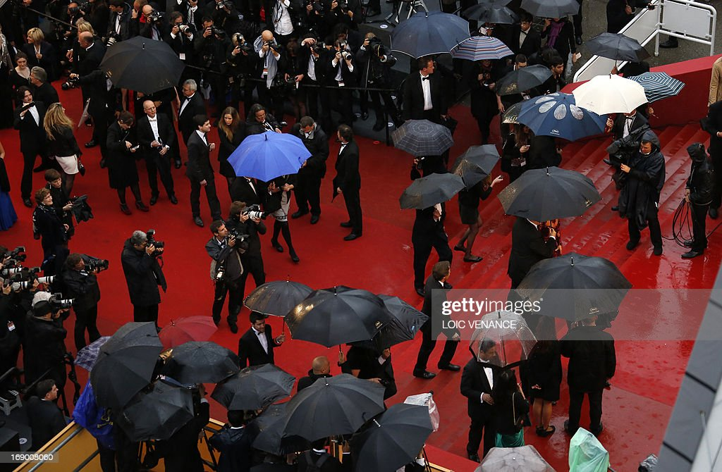 A general view shows people walking on the red carpet under pouring rain on May 18, 2013 before the screening of the film 'Jimmy P. Psychotherapy of a Plains Indian' presented in Competition at the 66th edition of the Cannes Film Festival in Cannes. Cannes, one of the world's top film festivals, opened on May 15 and will climax on May 26 with awards selected by a jury headed this year by Hollywood legend Steven Spielberg.