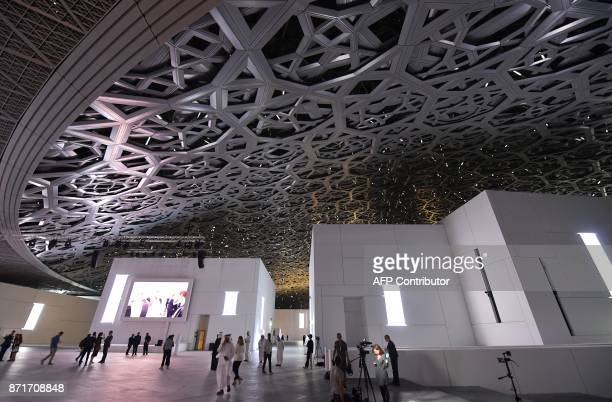 A general view shows people walking under the dome at the Louvre Abu Dhabi Museum that was designed by French architect Jean Nouvel during its...