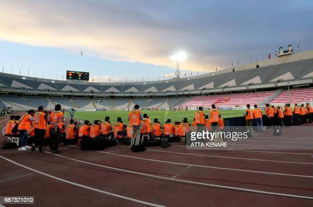 A general view shows photographer shooting in the empty stadium during the Asian Champions League football match between Qatar's Lekhwiya SC and...