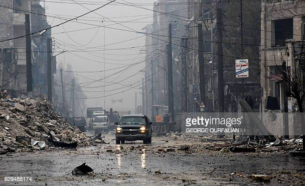 TOPSHOT A general view shows progovernment forces driving along a severely damaged street in Aleppo's newly captured AlKalasseh neighbourhood in the...