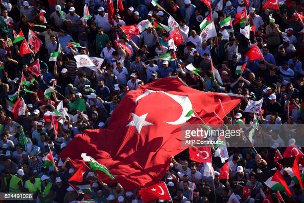 A general view shows protesters waving Turkish and Palestinian flags during a demonstration in Istanbul on July 30 to protest against measures taken...