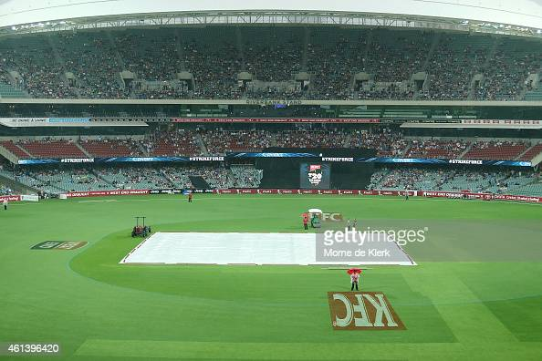 A general view shows rain and covers on the pitch before the Big Bash League match between the Adelaide Strikers and Sydney Thunder at Adelaide Oval...