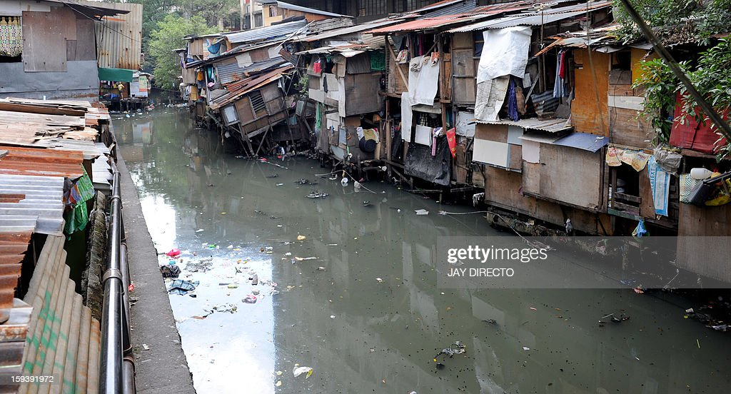 A general view shows shanty homes on the banks of a waterway in Manila on January 13, 2013. The Philippine government plans to move about 100,000 squatters from their homes on crucial waterways in Manila by June for their own safety and as a flood control measure, an official said on January 12. AFP PHOTO / Jay DIRECTO