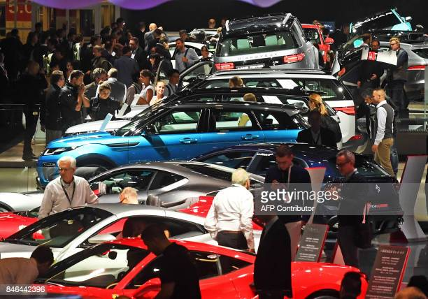 General view shows spectators visiting the hall in which Jaguar Land Rover and Ferrari are exhibited at the Frankfurt Auto Show IAA in Frankfurt am...