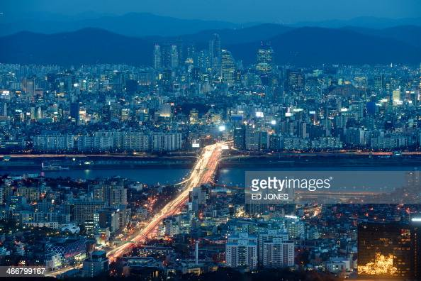 A general view shows the Gangnam area and Han river within the city skyline of Seoul at dusk on February 4 2014 With a population of some 25 million...