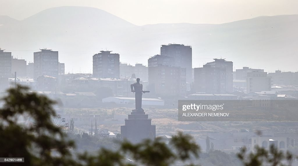 A general view shows the Mother Armenia monument and apartment buildings in Yerevan on June 25, 2016. / AFP / ALEXANDER