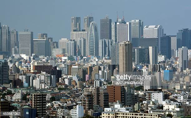 A general view shows the skyline of Shinjuku in Tokyo on August 13 2014 Japan's economy shrank in the latest quarter as a sales tax hike slammed the...