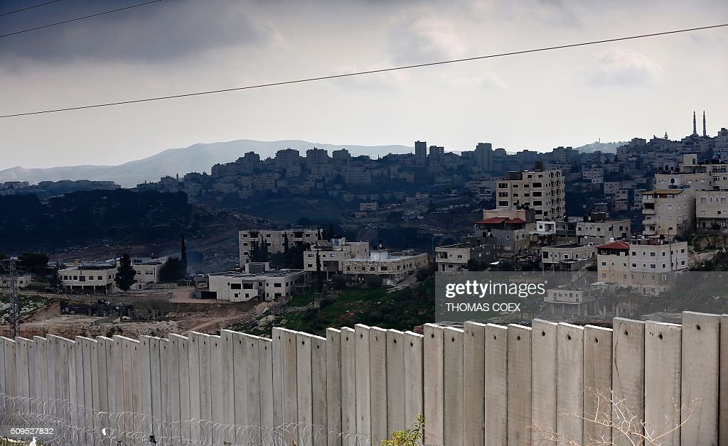 A general view shows the West Bank city of Abu Dis (background) behind Israel's controversial separation barrier dividing the Palestinian neighbourhood of Al-Tur in the Israeli annexed East Jerusalem with the West Bank, on February 11, 2016. / AFP / THOMAS COEX