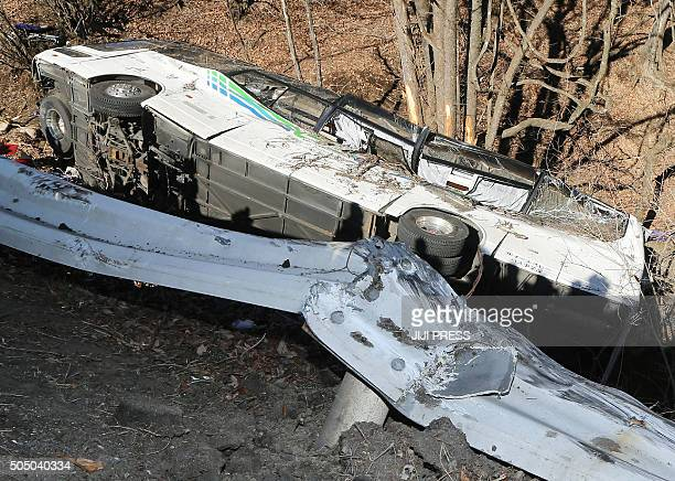 A general view shows the wreckage of a bus which crashed after running off a road in Karuizawa Nagano Prefecture on January 15 2016 Fourteen people...