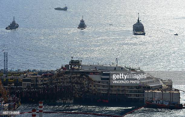 A general view shows tug boats near the wreck of the Costa Concordia cruise ship during an operation to refloat the liner on July 14 2014 off the...