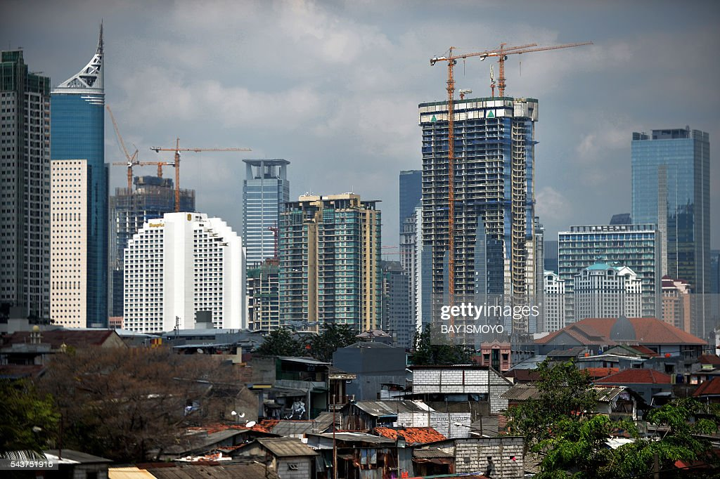 A general view shows under-construction buildings among the city skyline in Jakarta on June 30, 2016. Indonesia launched a tax amnesty in a bid to give Southeast Asias top economy a multibillion-dollar boost, defying criticism the move will let evaders off the hook. / AFP / BAY