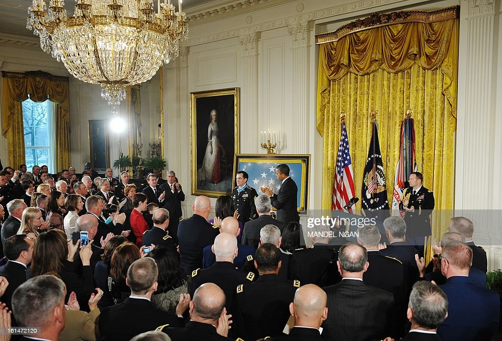 A general view shows US President Barack Obama and audience members applauding after Obama presented Clinton Romesha, retired duty Army staff sergeant, with the Medal of Honor during a ceremony in the East Room of the White House on February 11, 2013 in Washington. Romesha received the medal for conspicuous gallantry for actions taken on October 3, 2009 at at Combat Outpost Keating, Kamdesh District, Nuristan Province, Afghanistan. AFP PHOTO/Mandel NGAN