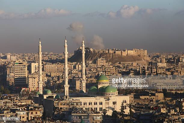 A general view taken from the governmentheld side of Aleppo shows smoke billowing near Aleppo's historic citadel during fighting between regime...