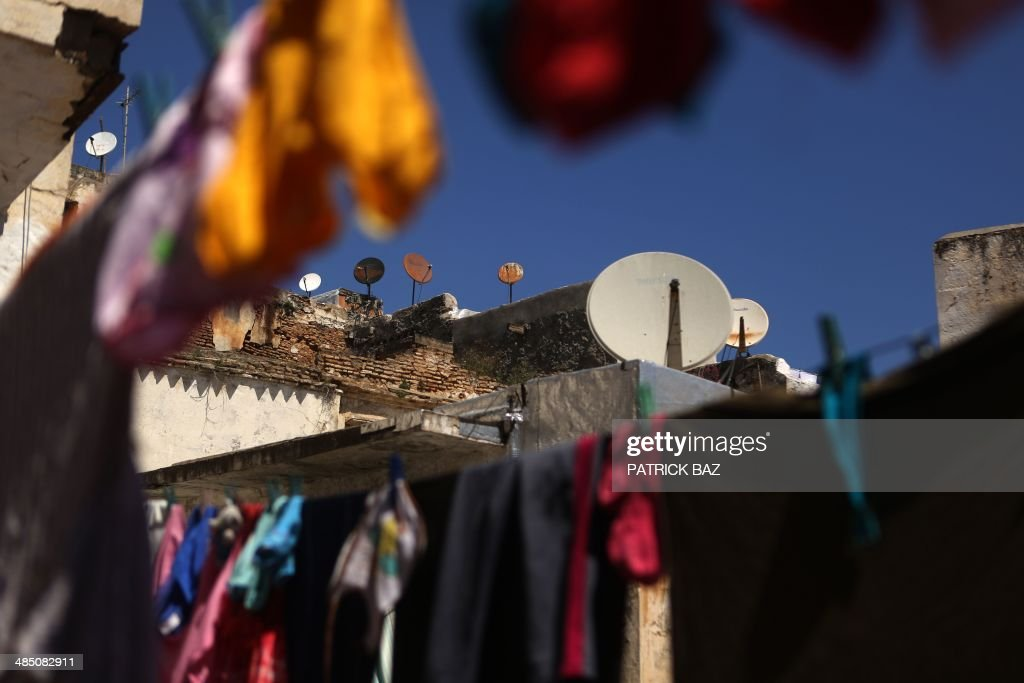 A general view taken on April 16, 2014 shows a building in the old part of Algiers, known as the 'Kasbah', covered with satellite dishes and hanging laundry.