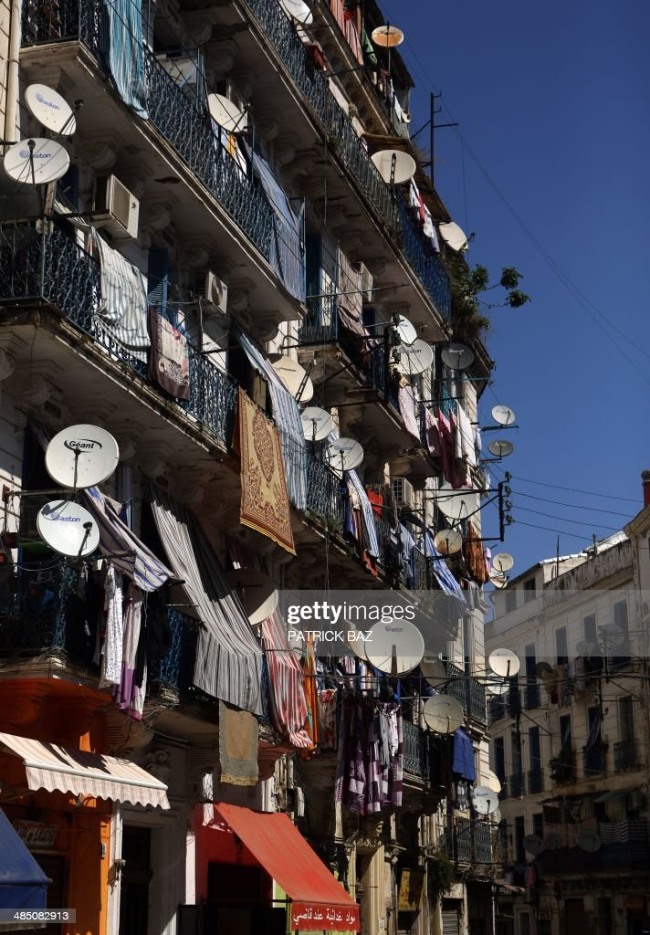 A general view taken on April 16, 2014 shows a building in the old part of Algiers, known as the 'Kasbah', which dates back to the French colonial era, covered with satellite dishes and laundry hanging on the balconies.
