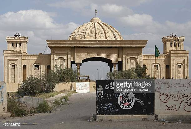 A general view taken on April 5 2015 shows a defaced Islamic State group flag in front of the main gate of palace of former Iraqi dictator Saddam...