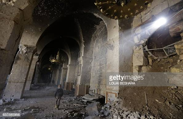 TOPSHOT A general view taken on January 22 2017 shows a boy walking under damaged arches at the ancient Umayyad Mosque in the old city of Aleppo a...