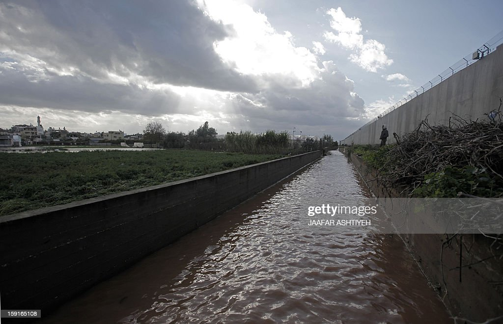 A general view taken on January 9, 2013 shows flooding next to the Israel's controversial separation barrier near the West Bank city of Qalqilya. Israel and the Palestinian territories have been lashed by heavy rain and high winds since January 6, which has caused flooding across the region. AFP PHOTO/JAAFAR ASHTIYEH