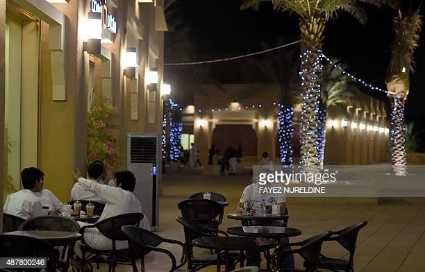 A general view taken on July 13 2015 shows Saudi men sitting in a coffee shop in the restored historical AlBureji area in the UNESCO World Heritage...
