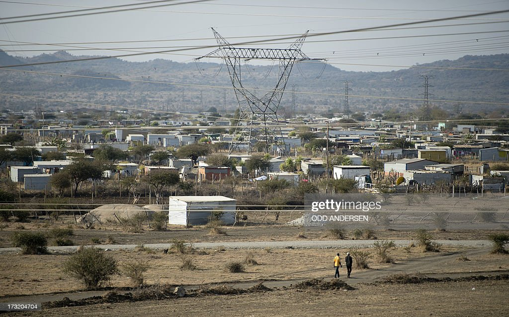 A general view taken on July 9, 2013 shows the Nkaneng shantytown next to the platinum mine, run by British company Lonmin, in Marikana. On August 16, 2012, police at the Marikana mine open fire on striking workers, killing 34 and injuring 78, during a strike was for better wages and living conditions. Miners still live in dire conditions despite a small wage increase.
