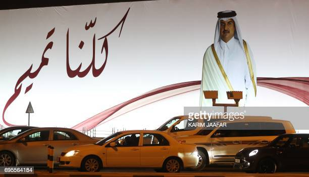 A general view taken on June 11 2017 shows a portrait of Qatar's Emir Sheikh Tamim bin Hamad AlThani and text reading in Arabic 'We are all Tamim' on...
