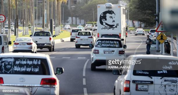 A general view taken on June 11 2017 shows portraits of Qatar's Emir Sheikh Tamim bin Hamad AlThani on the back of vehicles and text reading in...