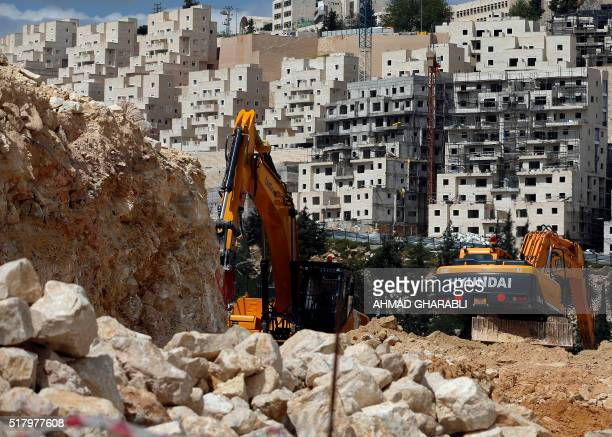 A general view taken on March 29 2016 shows Israeli construction cranes and excavators at a building site of new housing units in the Jewish...