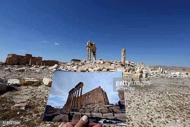 A general view taken on March 31 2016 shows a photographer holding his picture of the Temple of Bel taken on March 14 2014 in front of the remains of...