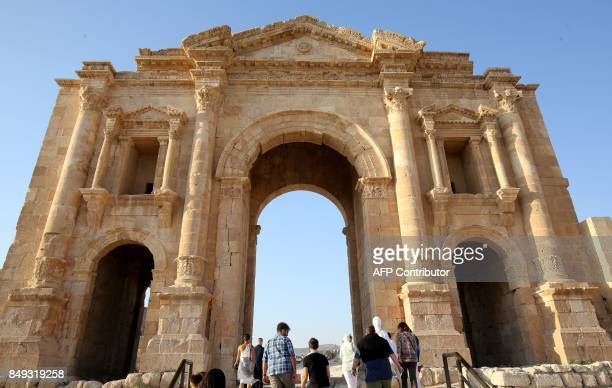 A general view taken on September 18 2017 shows tourists looking at Hadrian's Arch at the archaeological site of Jerash some 50 kilometres north of...