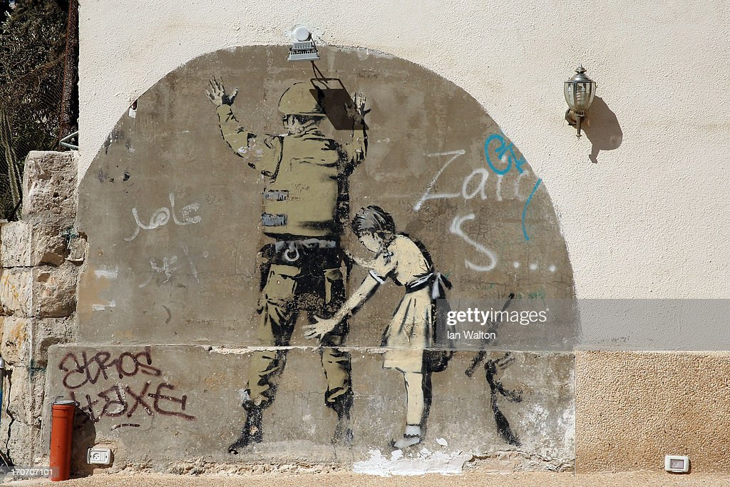 General views of a Banksy wall painting, on the apartheid wall near Bethlehem on June 16, 2013 in central West Bank.