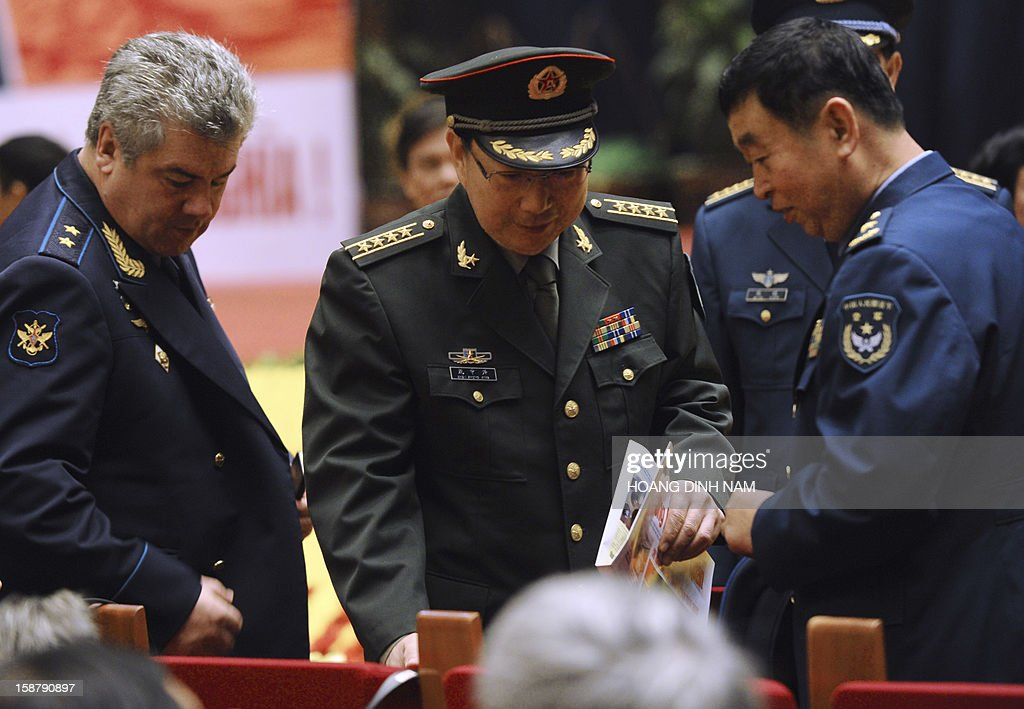 General Viktor Bondarev (L), Commander-in-Chief of Russian Airforce, and unidentified Chinese People's Army officers look for their seats prior to an event marking the 40th anniversary of 'Dien Bien Phu in the air' or victory over US Airforce B-52's Christmas bombing, in Hanoi on December 29, 2012. Hanoi claimed downing some 34 US B-52 aircrafts during the 12-day US bombing campaign in December 1972 over Hanoi and neighbouring provinces. The meeting is the final event of a month-long celebration organised by the government. AFP PHOTO/HOANG DINH Nam