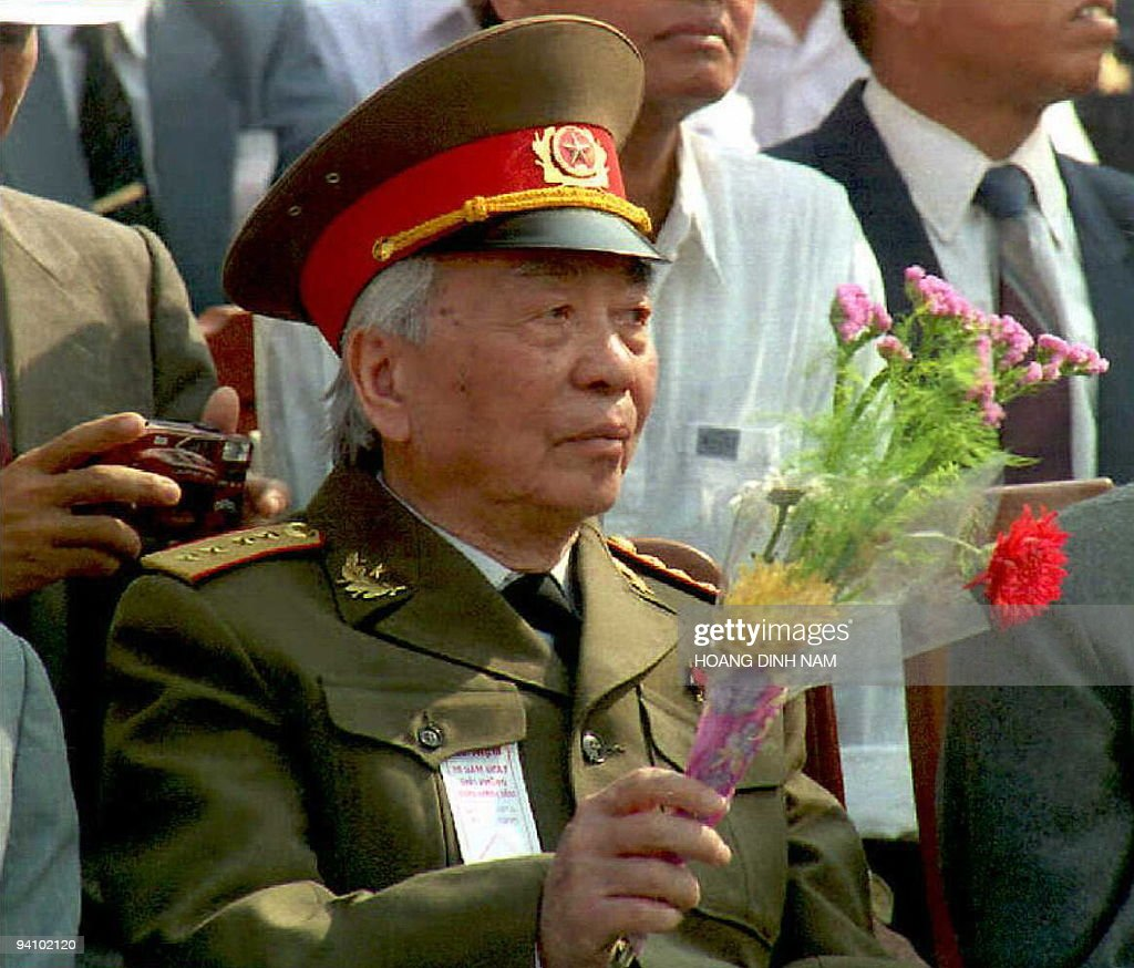 General Vo Nguyen Giap, whose forces defeated France, the US, and finally southern Vietnamese forces through years of fighting, waves flowers during a ceremony 29 March in Da Nang to mark the 20th anniversary of the city's fall near the end of the Vietnam War. The fall of this coastal city in central Vietnam preceded the fall of Saigon and the end of the war in April 1975. AFP PHOTO