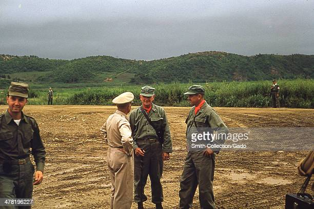 General William K Harrison Jr speaks to two US Army troops in orange bandanas at Peace Camp during the Korean War 1952 A patch of mud with tire...