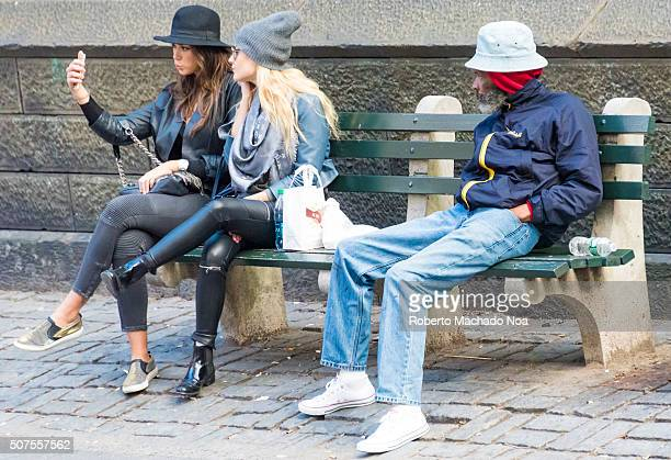 Generation Gap on everyday New York sceneYoung girls take a selfie seated in a bench in the streets of New York while a senior man watches