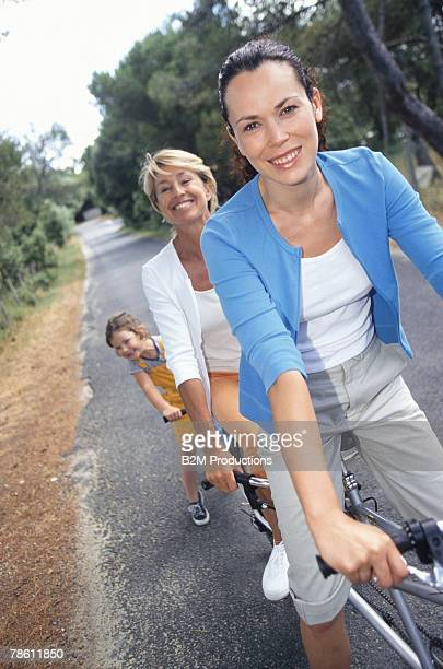 Generational family riding tandem bicycle