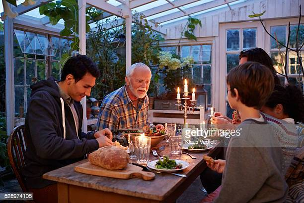3 generations having dinner in greenhouse
