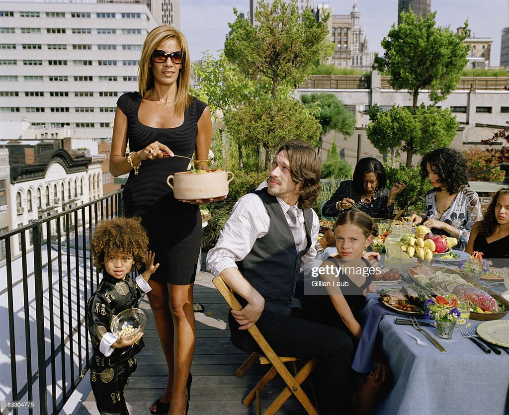 Generations of family having dinner on rooftop. : Stock Photo