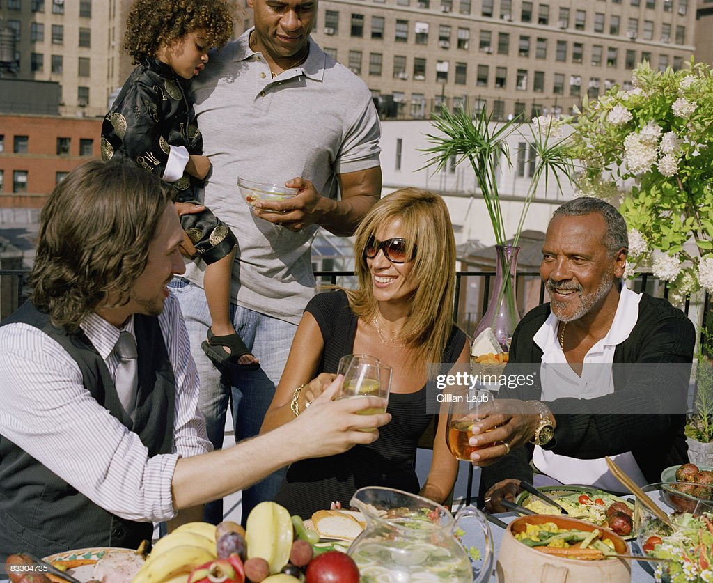 Generations of family having dinner rooftop. : Stock Photo
