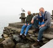Generations of men sitting on pier