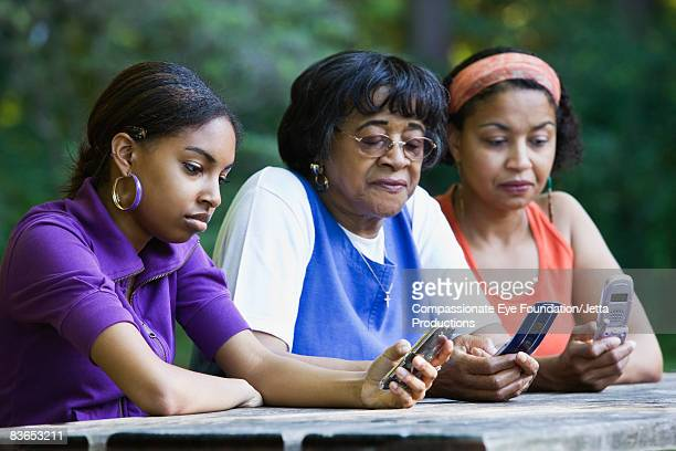 3 generations of women looking at cell phones