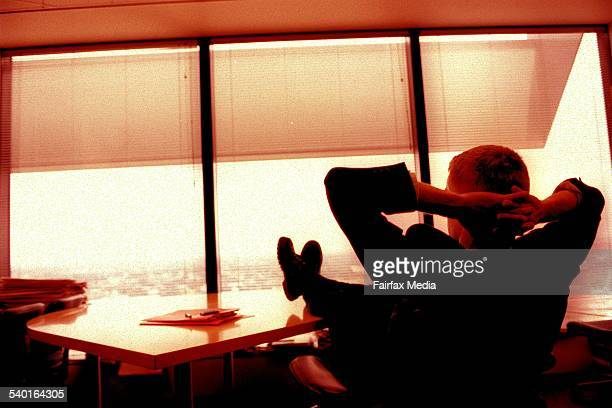 Generic businessman sitting at his desk with his feet up looking out of his executive suite window 16 February 2002 AFR Picture by LOUISE KENNERLEY